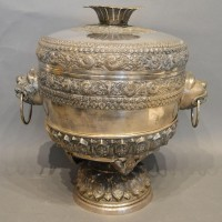 An Indian White Metal Large Covered Vase on Stand, the shaped cover above mask ring handles and circular pedestal stand Hammer £1,100